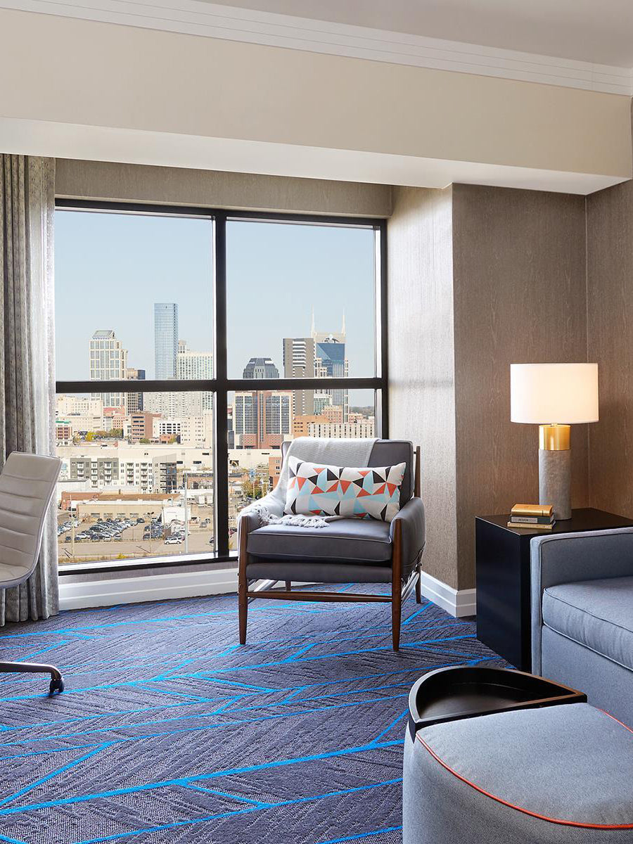 Hutton Hotel, Nashville - hotel room with grey furniture, blue patterned carpet, and a large window overlooking the city