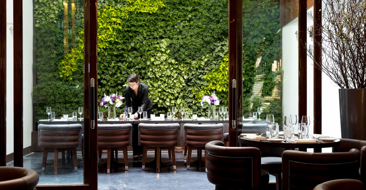 Hotel Hugo, NYC - woman setting an outdoor table in front of a plant wall background