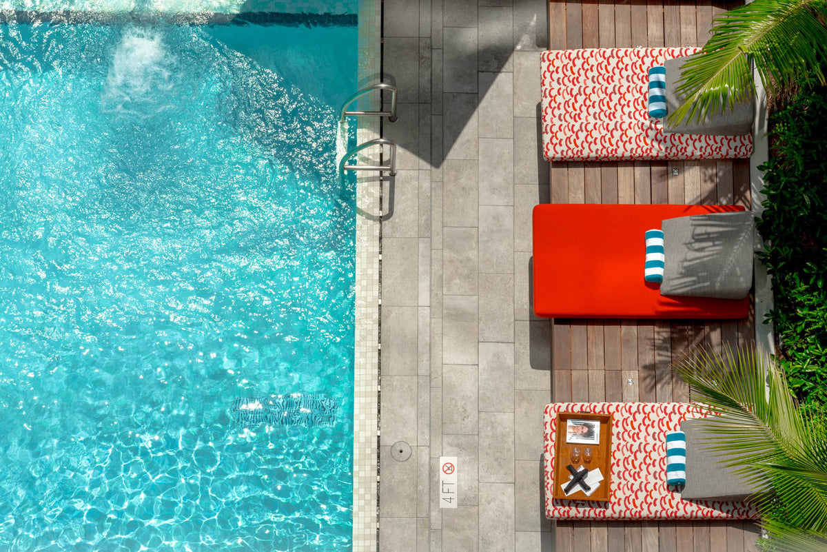 EAST, Miami - bird's eye view of a pool with three red patterned lounge beds and palm trees