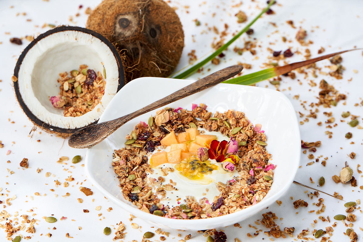 ECO Lifestyle + Lodge, Barbados - white square bowl with yogurt, granola, and local fruit next to open coconut
