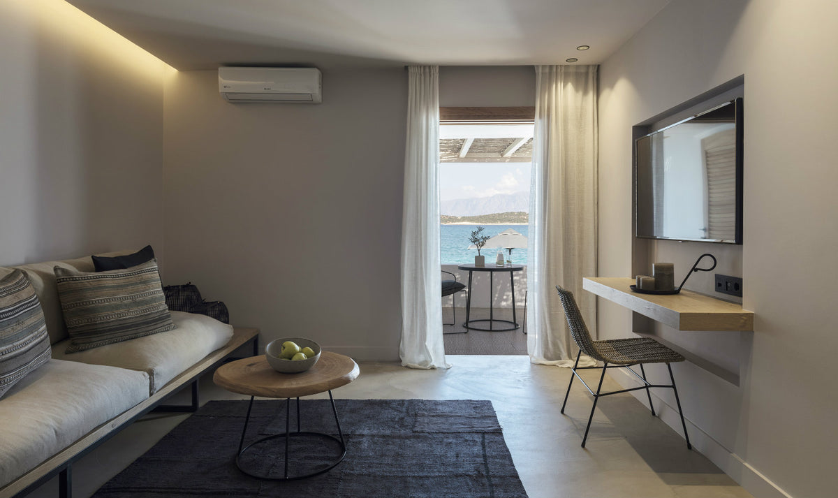 Minos Beach Art Hotel, Crete - hotel room with desk, chair, couch, tv, and curtained window leading to a private ocean view patio