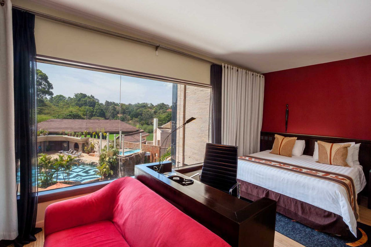 Tribe, Nairobi - hotel room with red accent wall, red couch, bed, decorative pillows, and view of pool