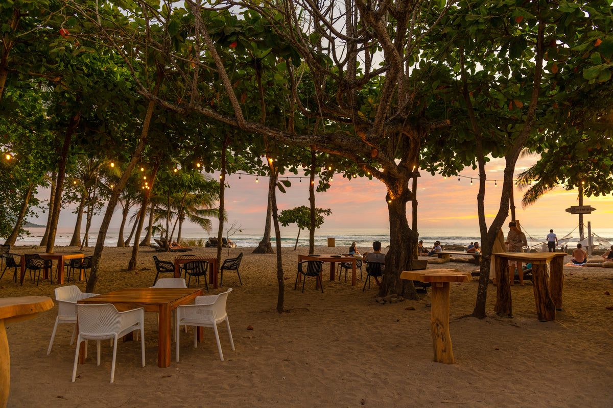 Nantipa, Santa Teresa, Costa Rica - Manzu restaurant with tables and chairs on the beach under large trees at sunset