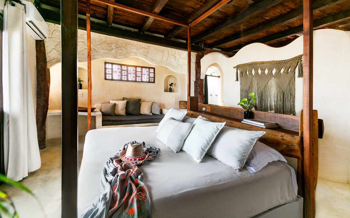 Amansala, Tulum - rustic hotel room with wooden ceiling, canopy bed, and couch