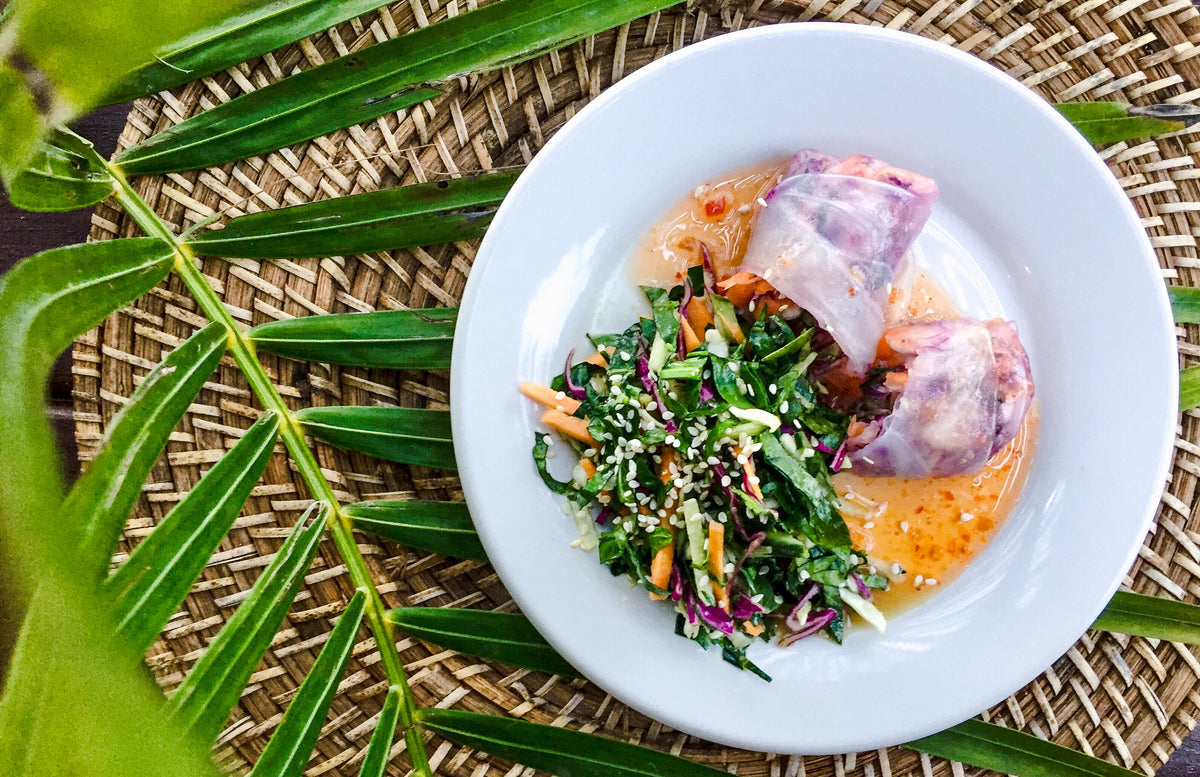 Amansala, Tulum - white plate with vegetable salad and vegetable spring rolls on a wicker and palm frond background