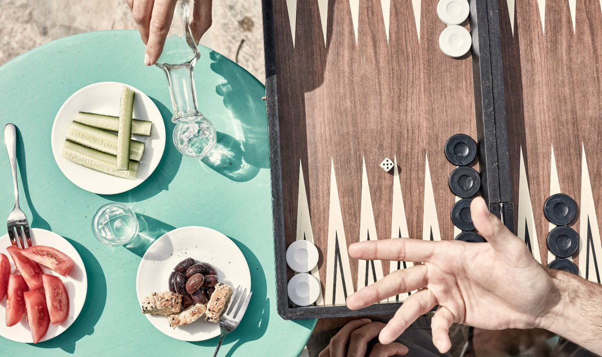 Minos Beach Art Hotel, Crete - close up of vegetable plates, hands, and a backgammon board