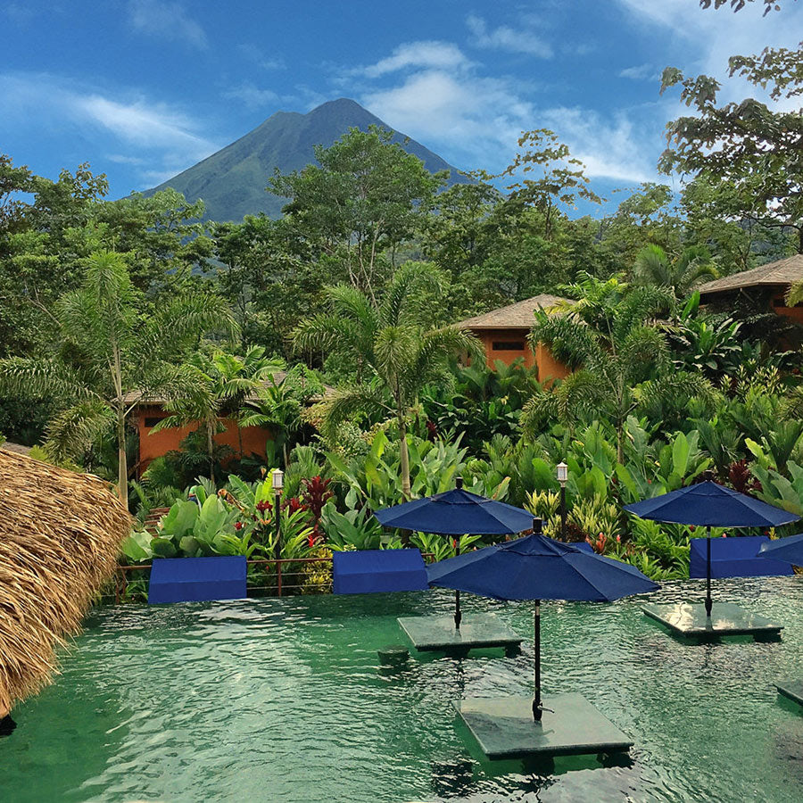 Nayara Resorts, Arenal - hotel pool with tables in the water, blue sun umbrellas, and jungle scenery view