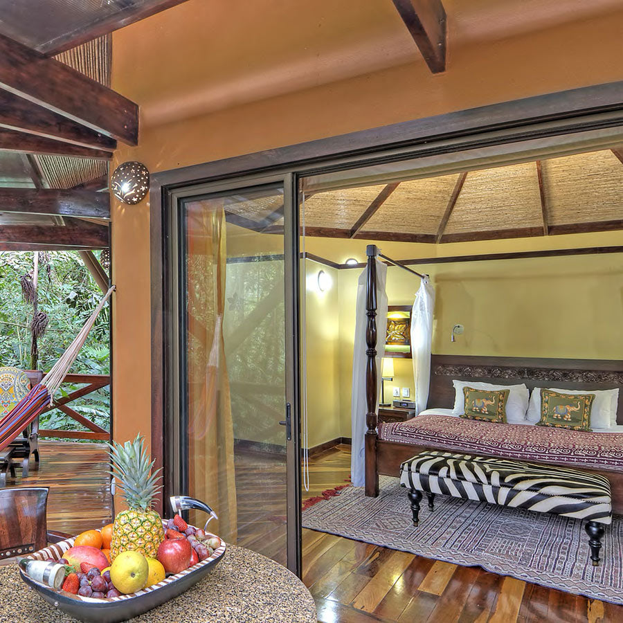 Nayara Resorts, Arenal - hotel patio with hammock, table with fruit bowl, and sliding doors leading to bedroom with canopy bed