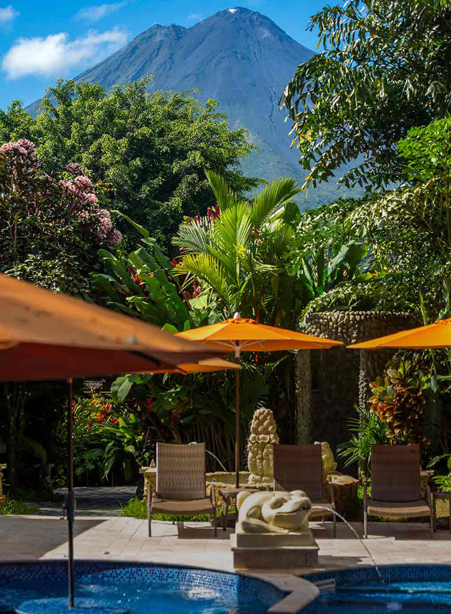 Nayara Resorts, Arenal - resort pool with orange sun umbrellas, lounge chairs, jungle scenery, and a mountain in the background