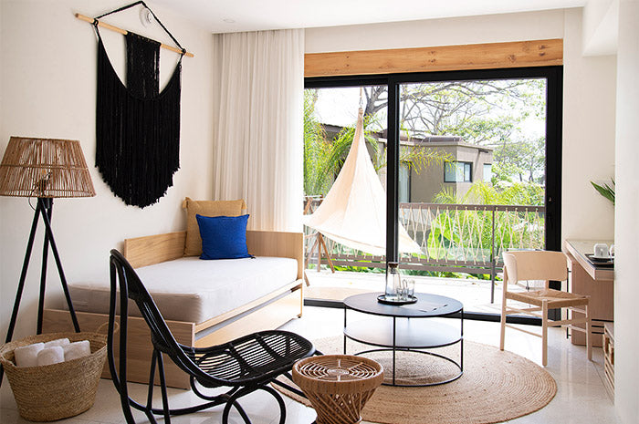 Nantipa, Santa Teresa, Costa Rica - hotel room with neutral wood decor, black accent chair, and floor to ceiling sliding door overlooking jungle