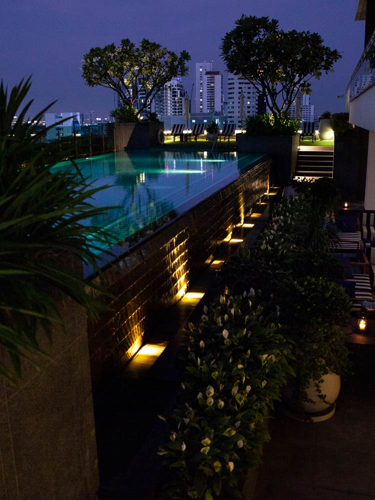 Akyra Thonglor, Bangkok - rooftop pool with greenery, lounge chairs, and a nighttime city view