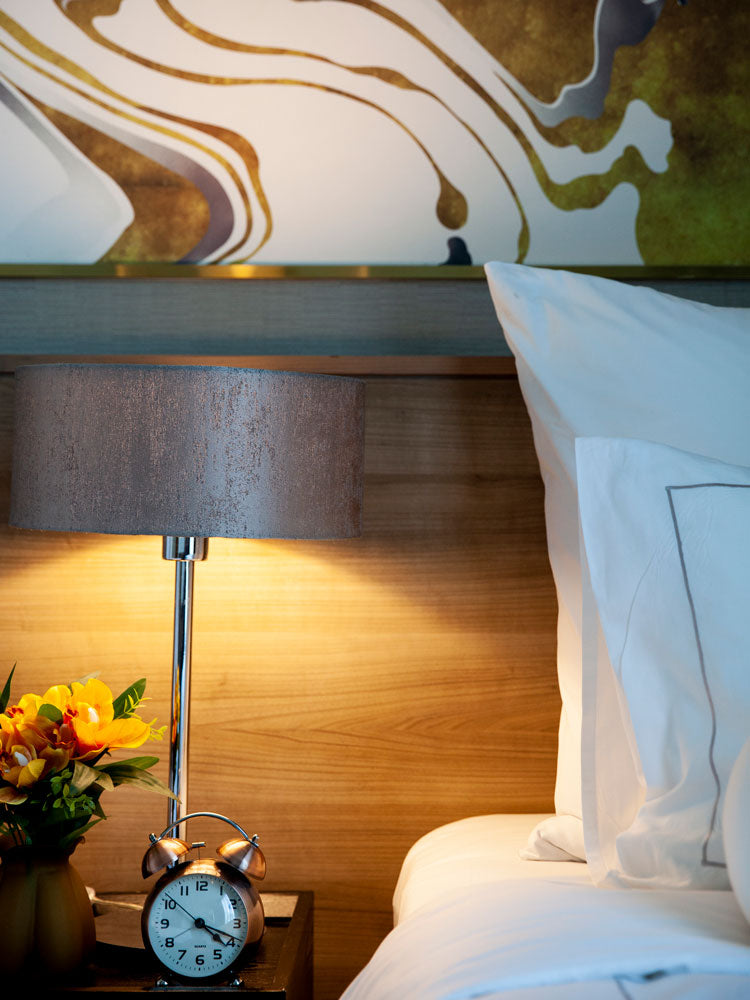 Akyra Thonglor, Bangkok - close up of a hotel bedside table with flowers in a vase, a lamp, an alarm clock, and marbled wallpaper