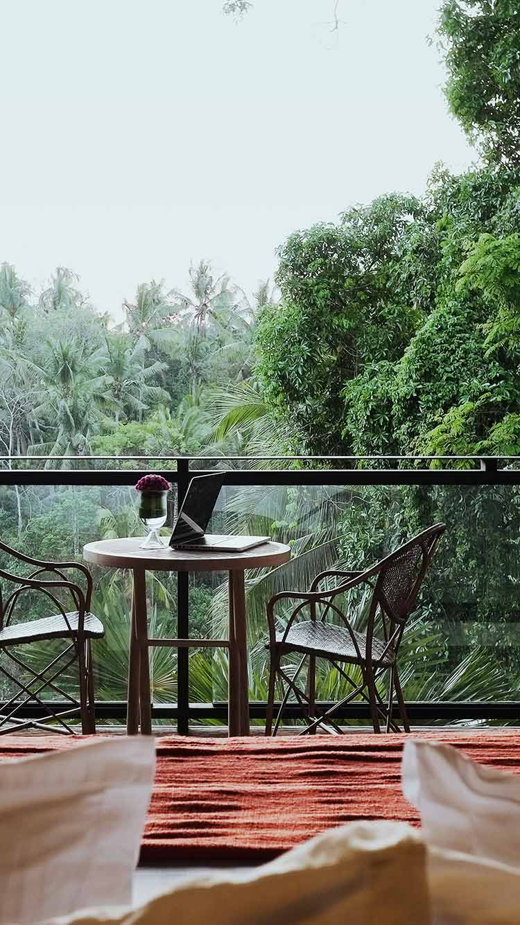 Bisma Eight, Bali - balcony with table, chairs, and orange rug overlooking jungle