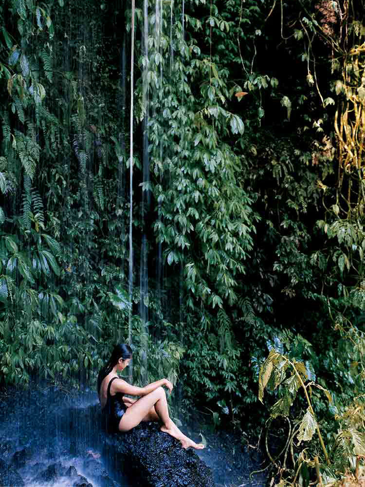 Bisma Eight, Bali - woman sitting on a rock under a small waterfall with a plant covered backdrop