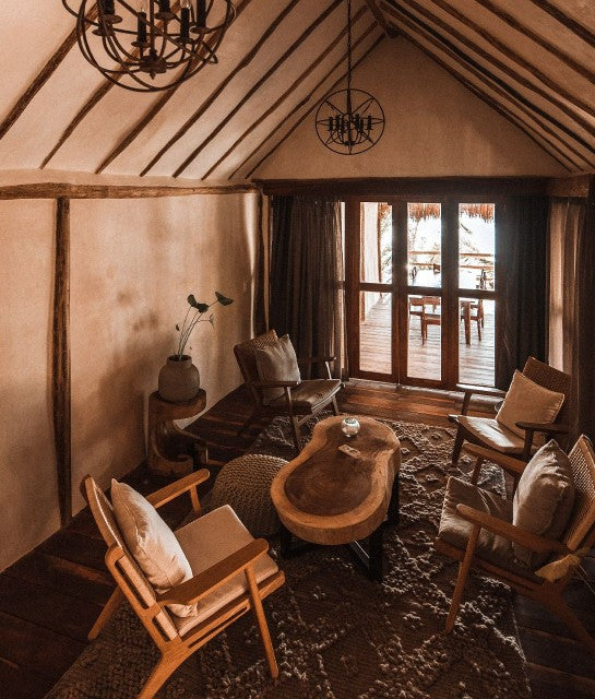 Papaya Playa Project, Tulum - hotel room with rustic wooden chairs, rustic wooden coffee table, wooden beam decoration, and door overlooking private patio