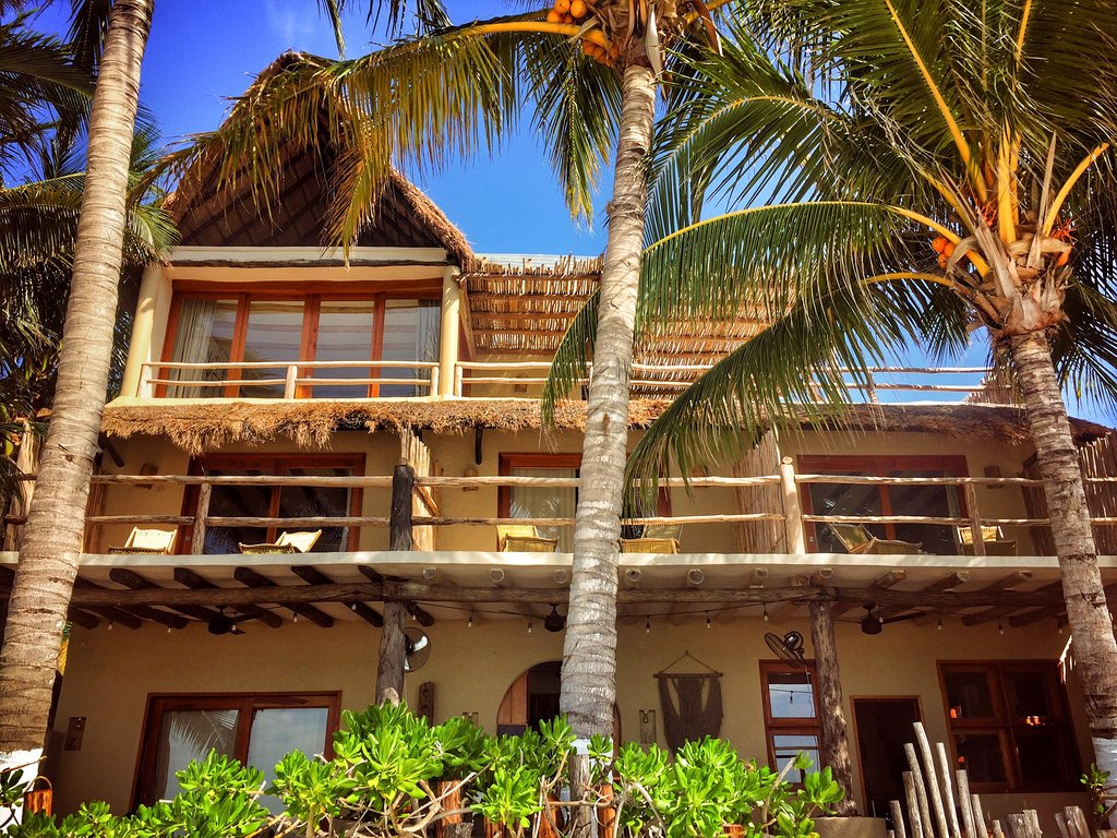 Casa Cat Ba, Isla Holbox - exterior view of rustic wooden villa with balconies and palm trees