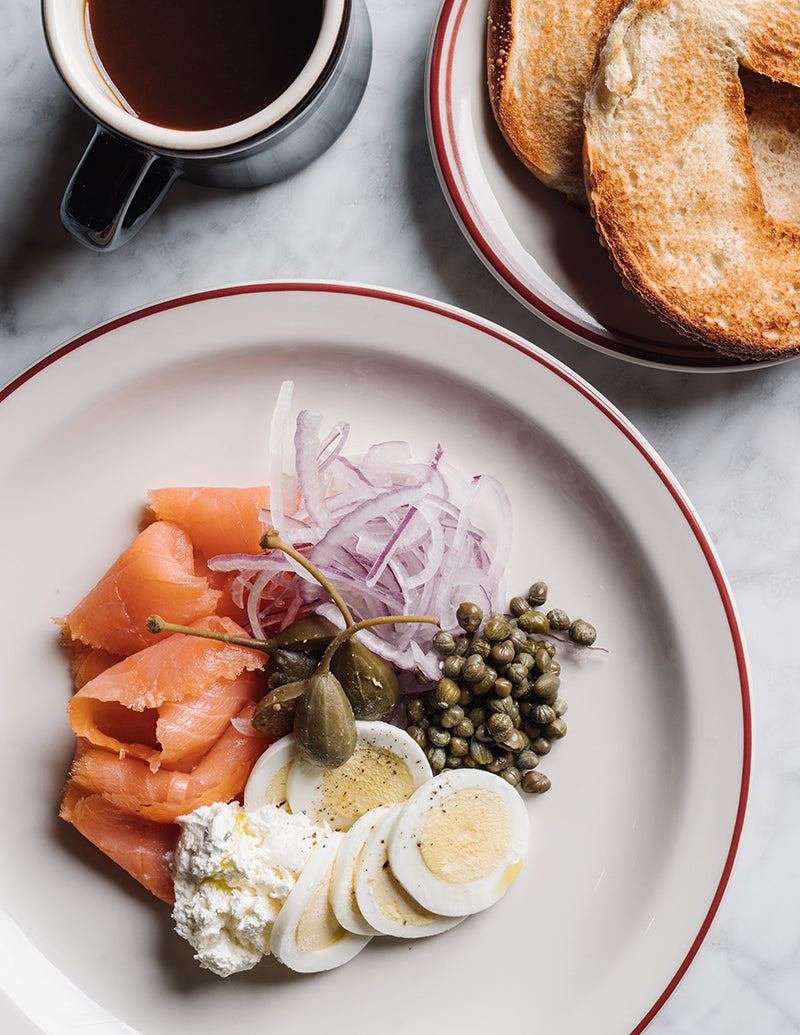 The Alida, Savannah - close up of circular plate with lox, hard boiled egg, cream cheese, capers, red onions, and bagel on the side