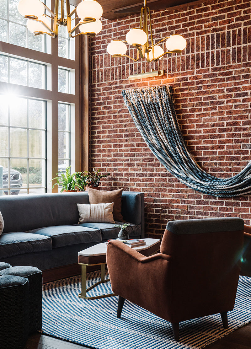 The Alida, Savannah - hotel lounge with brick walls, brown armchairs, and blue sofa