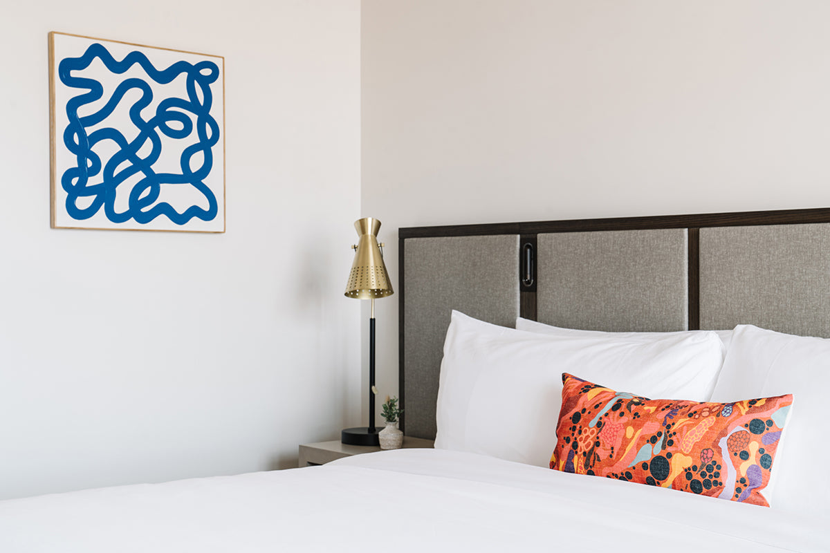 The Alida, Savannah - hotel bed with fabric headboard, bright decorative pillow, and hanging abstract blue sketch