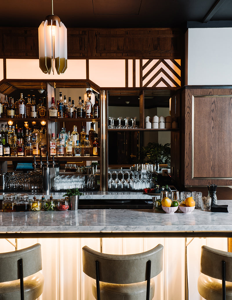 The Alida, Savannah - Trade Room lobby bar with vintage wood cabinets, stocked alcohol shelves, marble bar top, and leather barstools