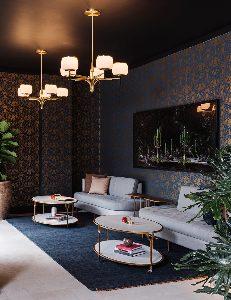 The Alida, Savannah - contemporary hotel lounge with gold and blue wall paper, grey couches, and chic white coffee tables