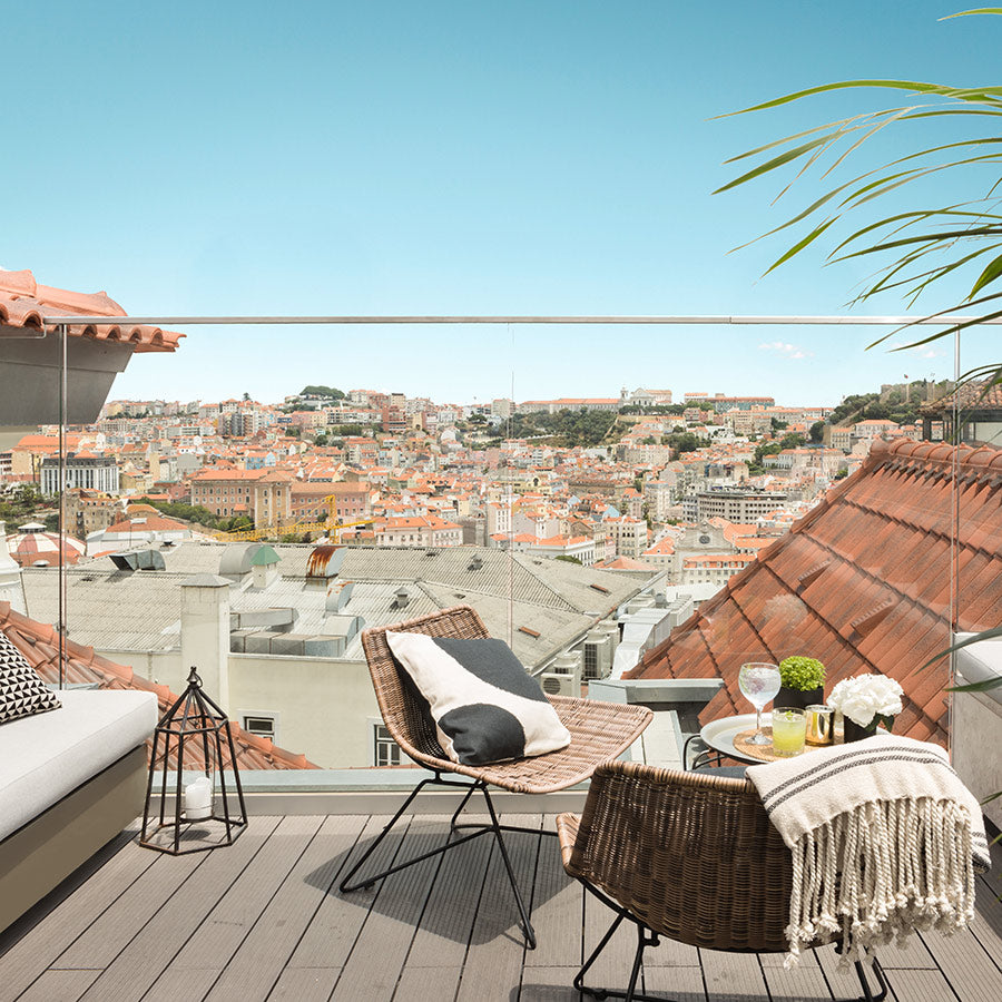 The Lumiares, Lisbon - hotel rooftop lounge with couches, chairs, and view of the city in daytime
