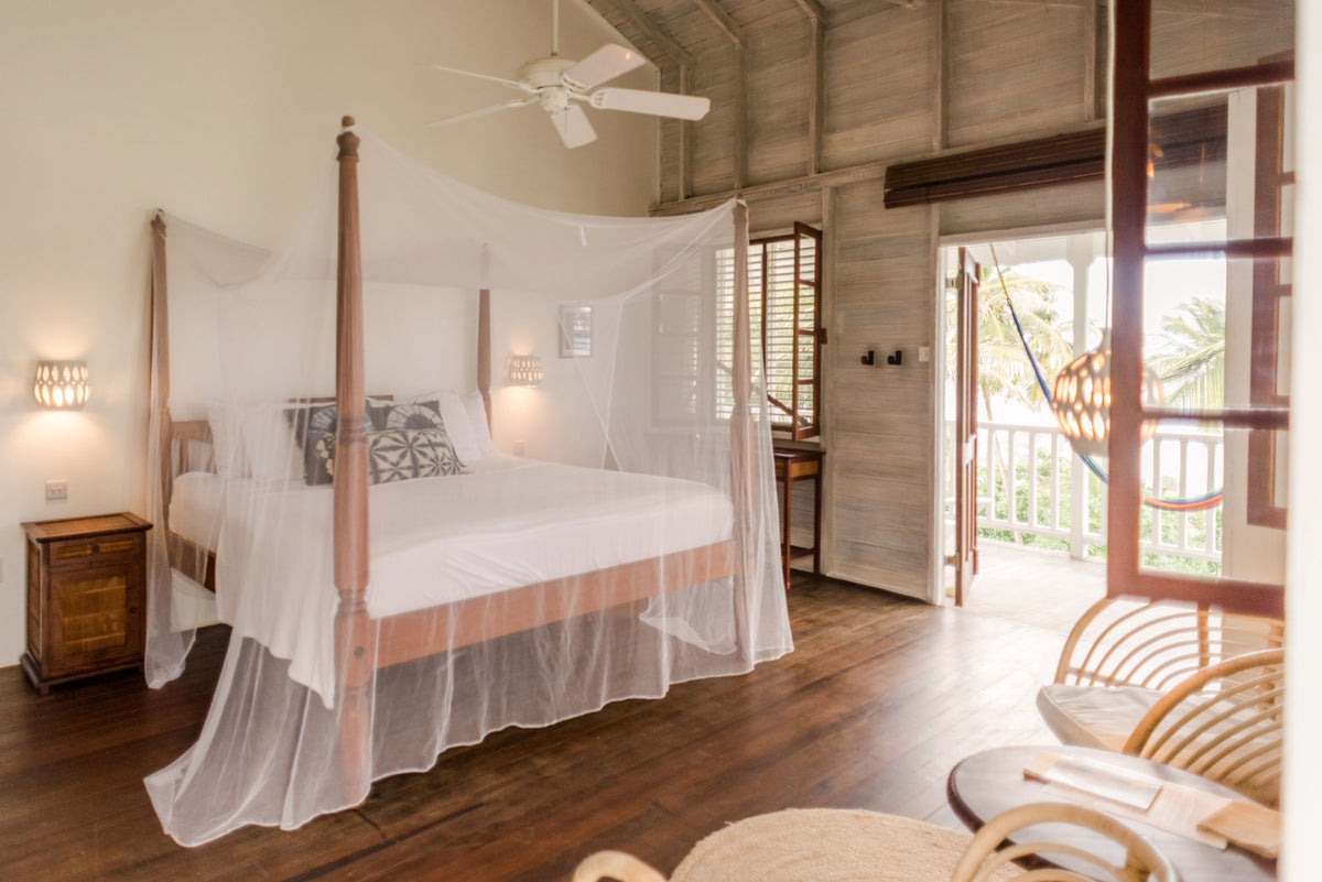 ECO Lifestyle + Lodge, Barbados - hotel room with wood walls, wicker chairs, and four posted bed with mosquito net