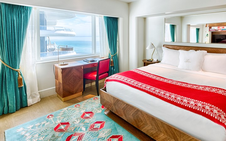Faena Hotel, Miami Beach - hotel bed with vintage decorations, red and teal theme, and large window overlooking ocean