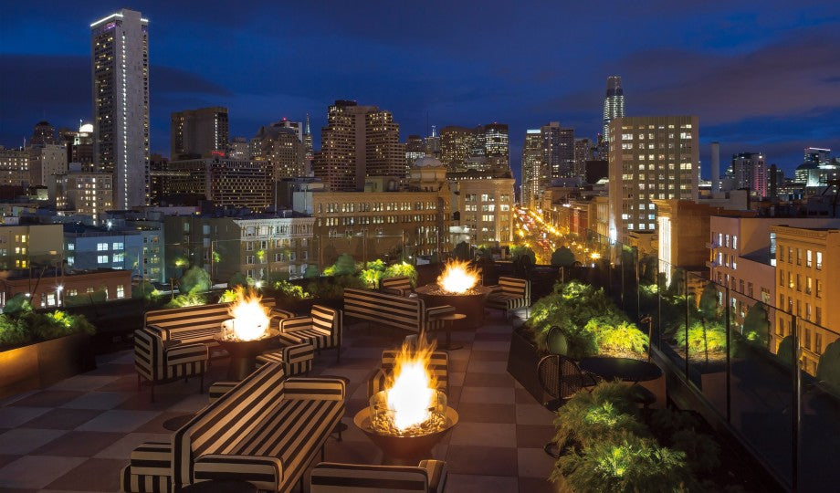San Francisco Proper Hotel, San Francisco - hotel rooftop lounge with striped black and white couches, potted plants, and city view at night
