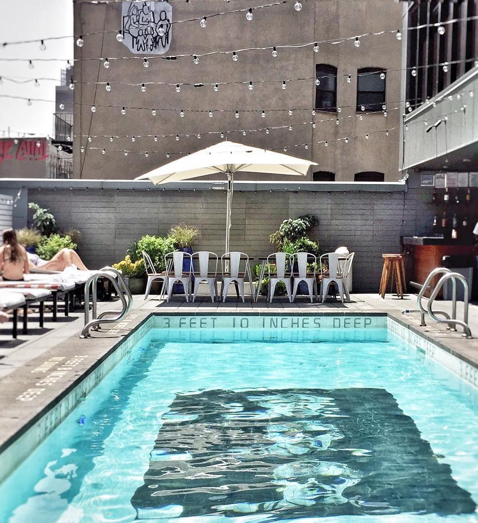 Sixty LES, NYC - rooftop pool with people on white lounge chairs, white metal chairs, string lights, and white sun umbrella