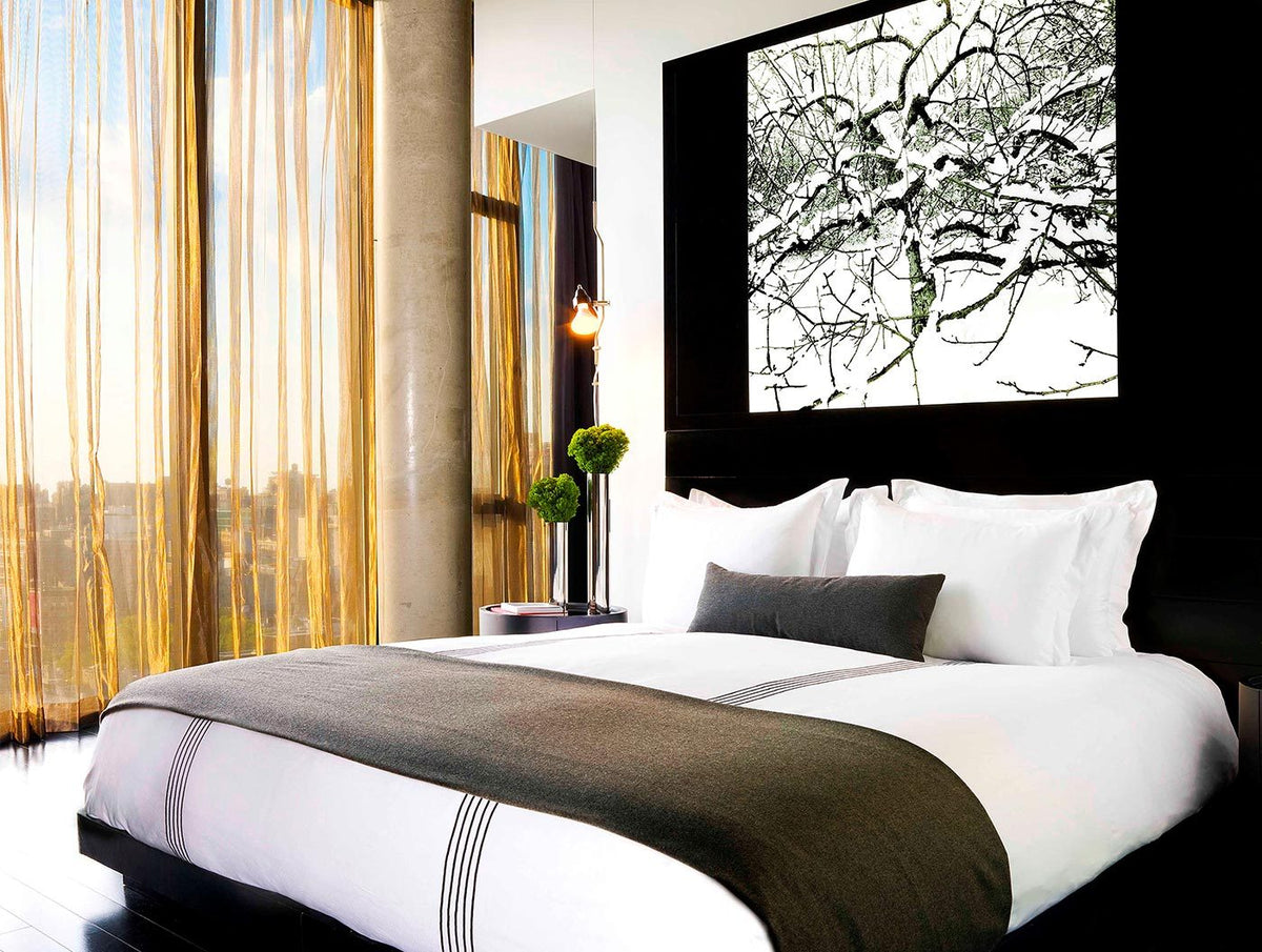 Sixty LES, NYC - hotel room with bed, snowy tree photo headboard, and sheer gold curtains over floor to ceiling windows