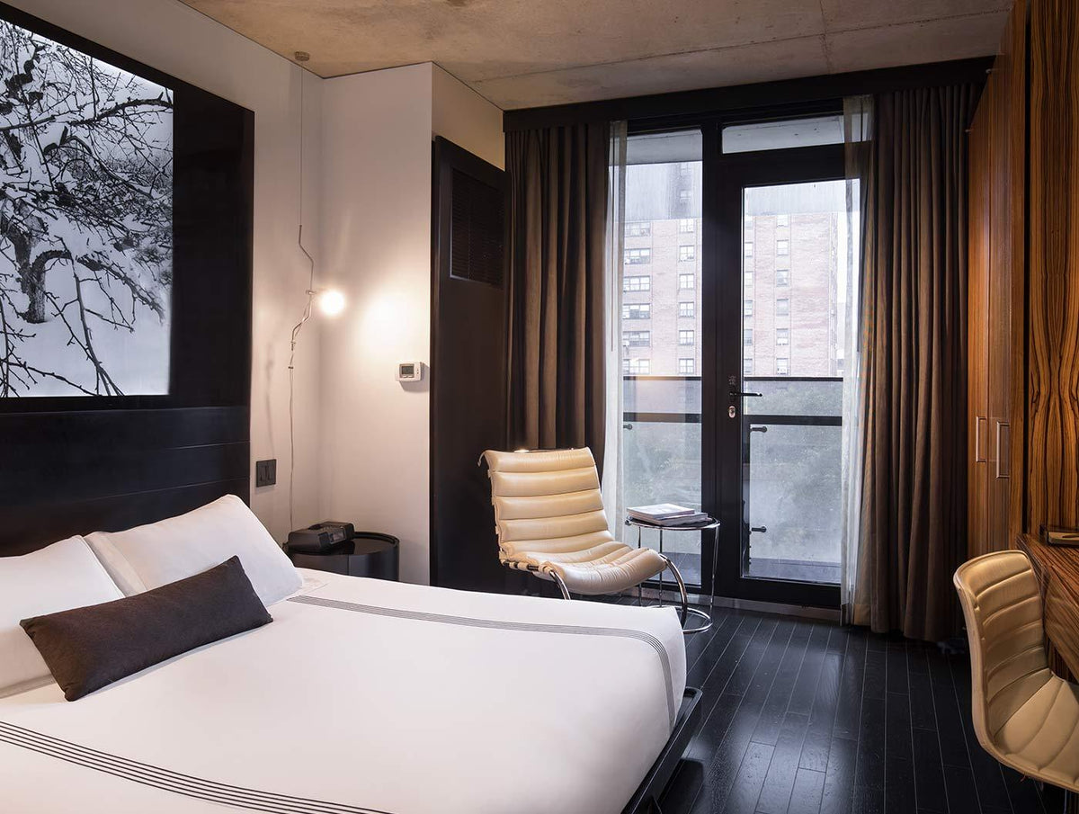Sixty LES, NYC - hotel room with dark interior, white and beige furniture, and door leading to private balcony