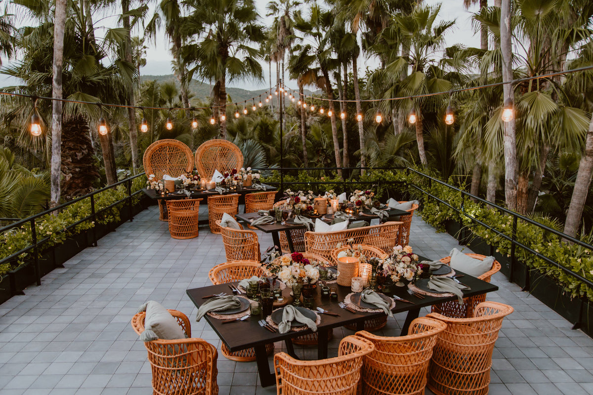 Acre, Los Cabos - outdoor patio with wicker chairs, set tables, and string lights in jungle setting