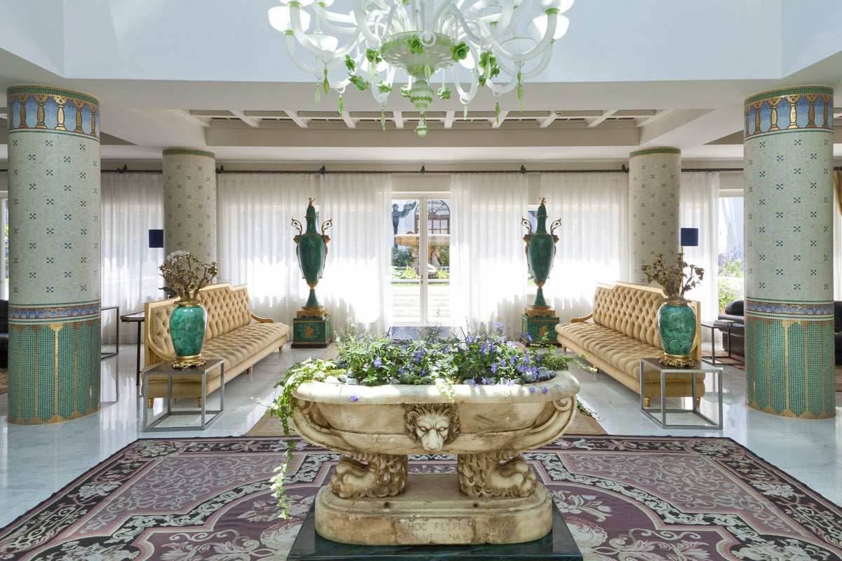 Terme Manzi Hotel & Spa, Ischia - opulent old world style room with columns, gold couches, and stone tub with plants