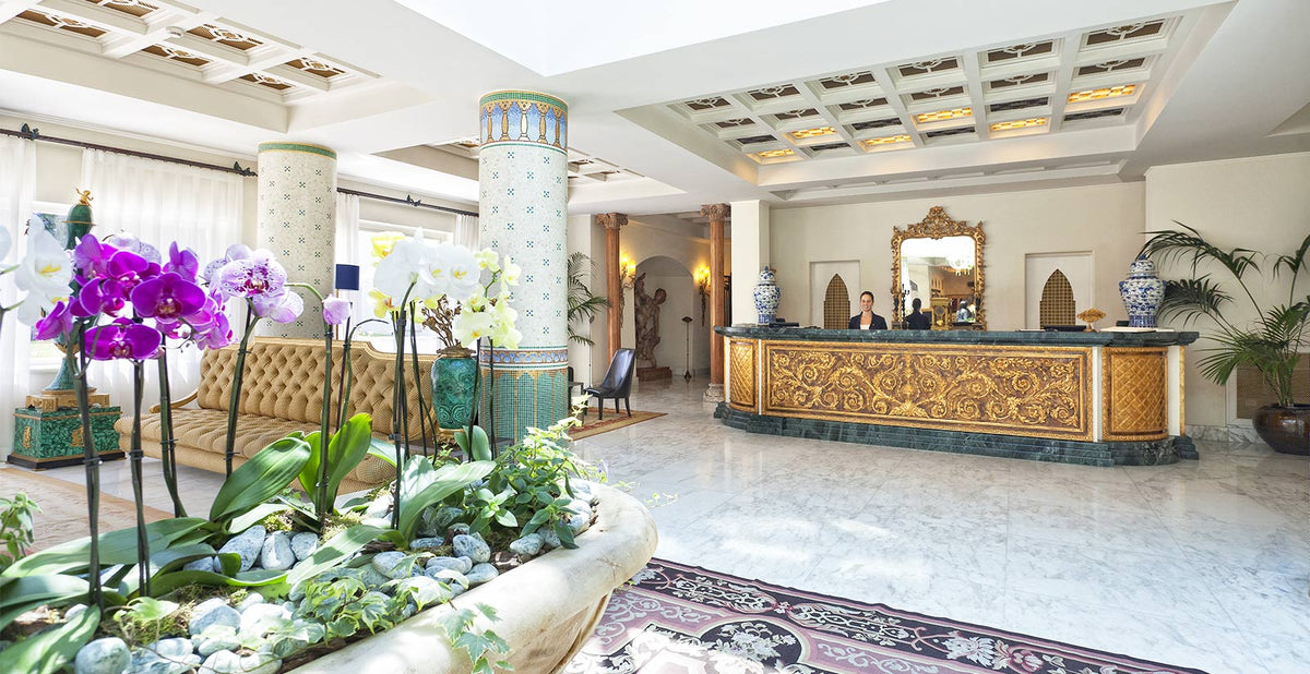 Terme Manzi Hotel & Spa, Ischia - Roman style hotel lobby with stone column, marble floor, and intricate golden reception desk