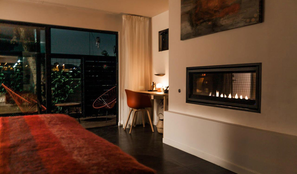 Twelve Senses Retreat, Encinitas - hotel room with bed, desk, chair, private balcony, and fireplace at night