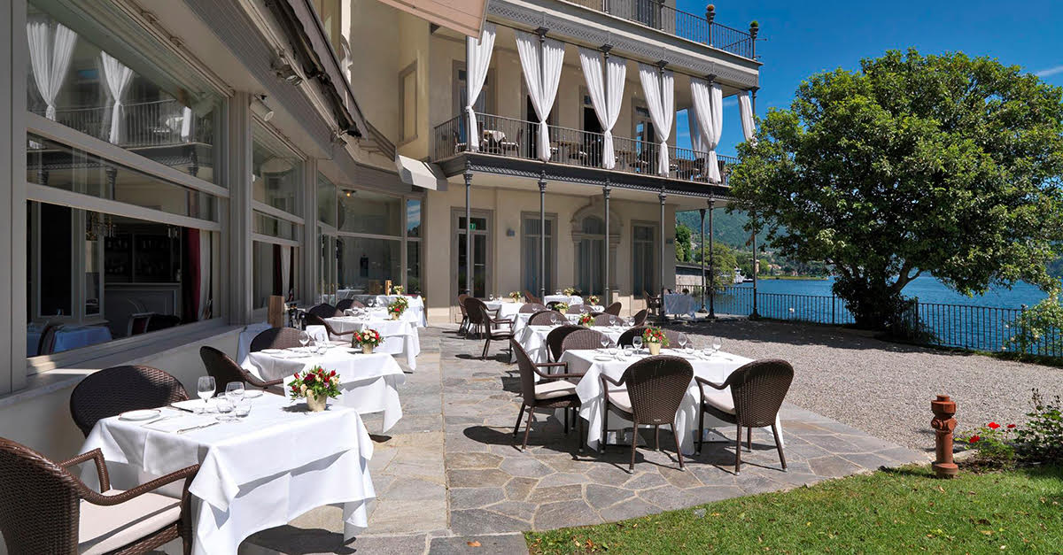 Hotel Villa Flori, Lake Como - hotel courtyard with outdoor dining tables, balconies, and a view of Lake Como