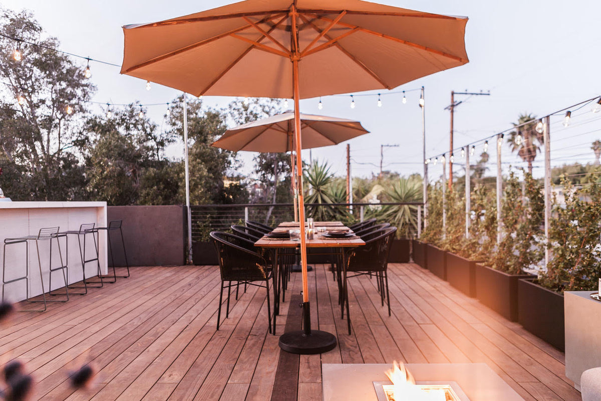 Twelve Senses Retreat, Encinitas - hotel rooftop with set table, sun umbrellas, and a bar with barstools