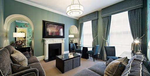 Flemings Mayfair, London - blue grey walled hotel room with grey sofas and lamps with circular lampshades