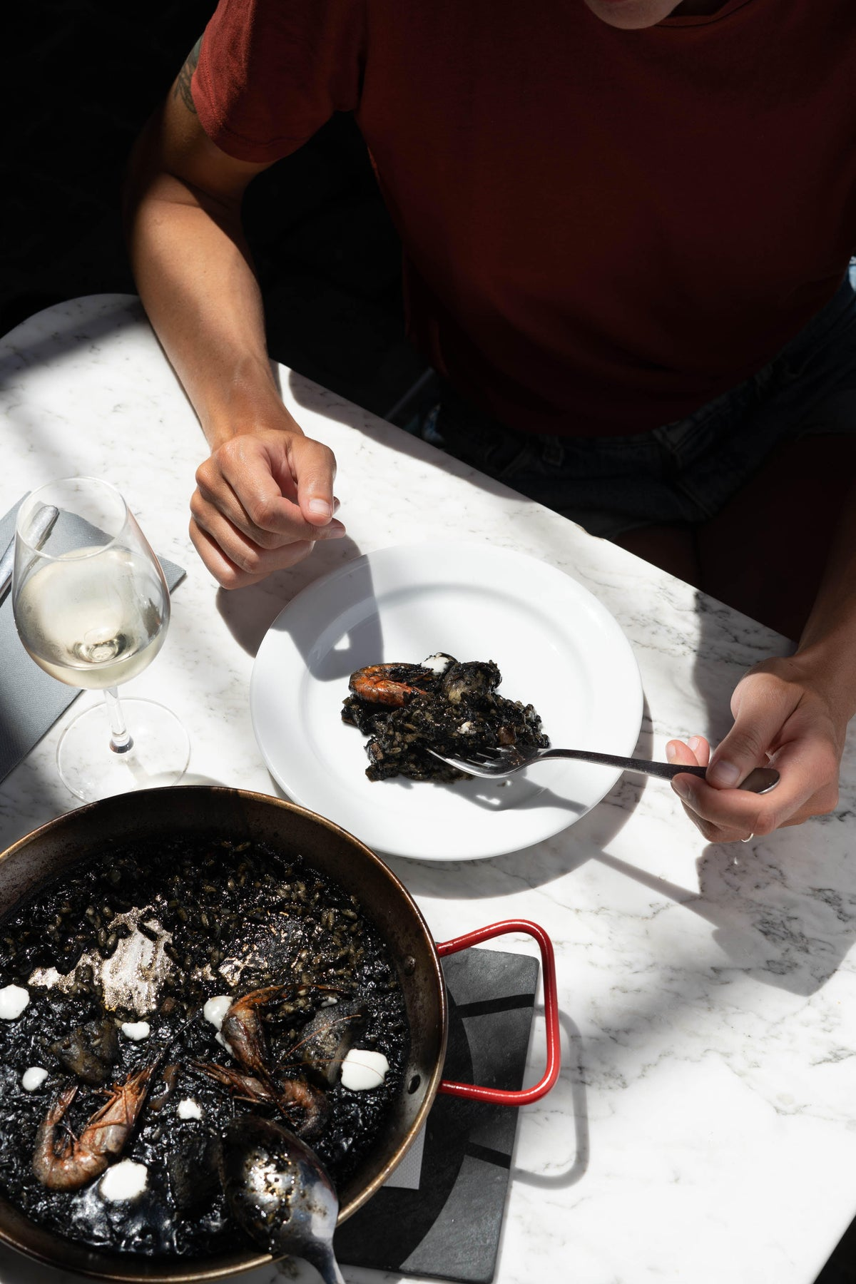 Hotel Brummell, Barcelona - pan of black paella with someone eating a plate of paella