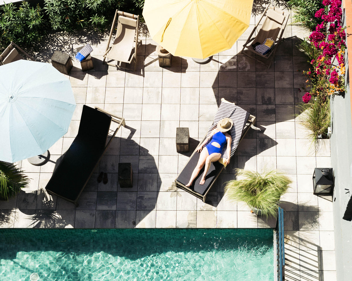 Hotel Brummell, Barcelona - birds eye view of a woman lounging on a chaise next to a pool with colorful sun umbrellas