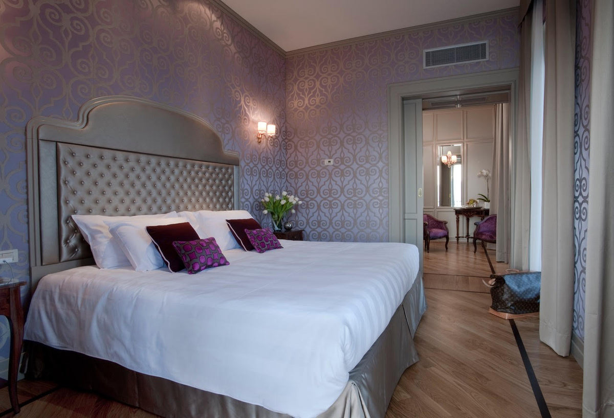 Hotel Villa Flori, Lake Como - hotel room with a king size bed, silk headboard, and ornate purple silk walls