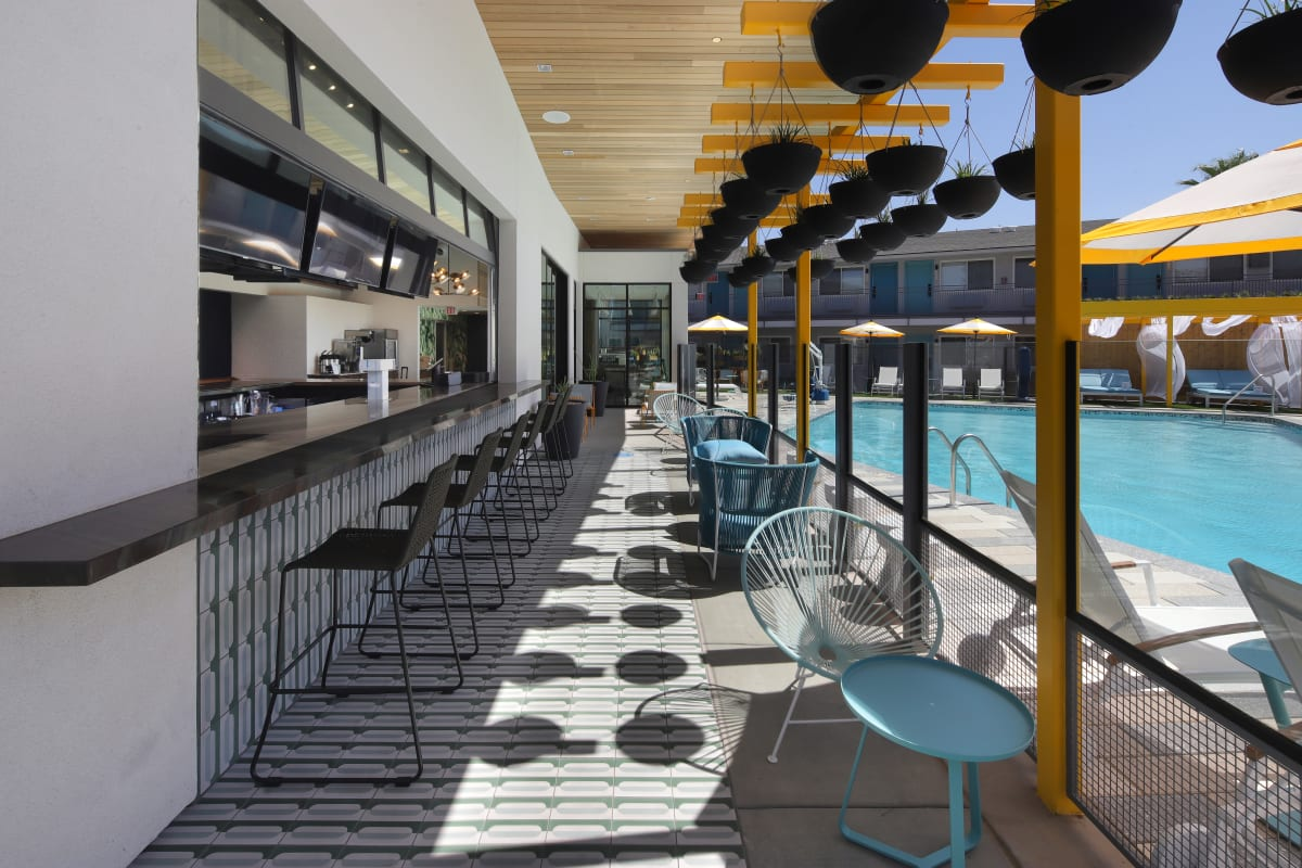 The Tuxon Hotel, Tucson - hotel pool with bar, seating, hanging planters, and yellow sun umbrellas