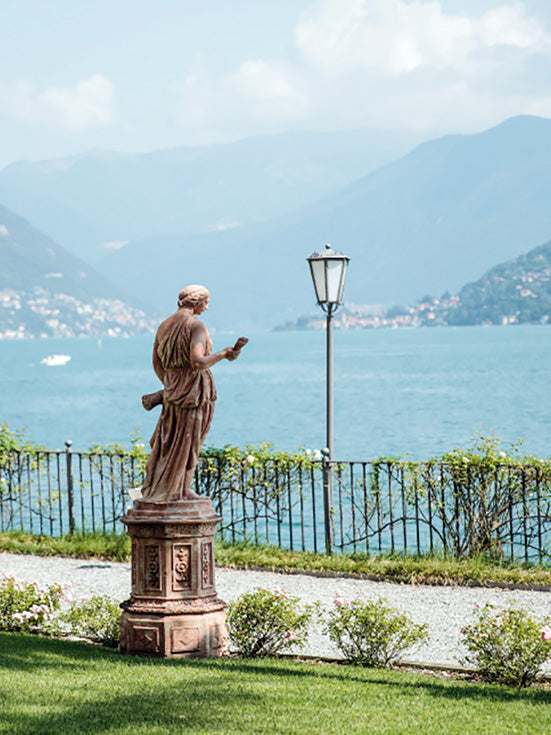 Hotel Villa Flori, Lake Como - ancient stone statue of a woman in front of an iron fence and a view of Lake Como