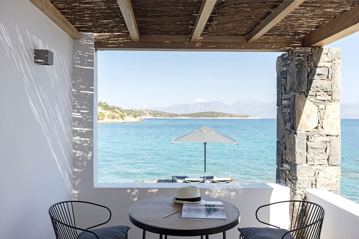 Minos Beach Art Hotel, Crete - patio with table, chairs, wooden ceiling, and view of Aegean sea