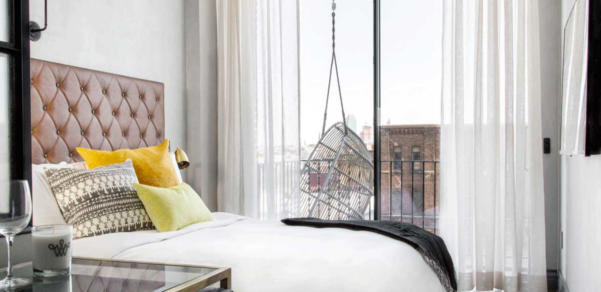 The Williamsburg Hotel, NYC - hotel room with bed, large windows, and private balcony with a hanging wicker swing chair
