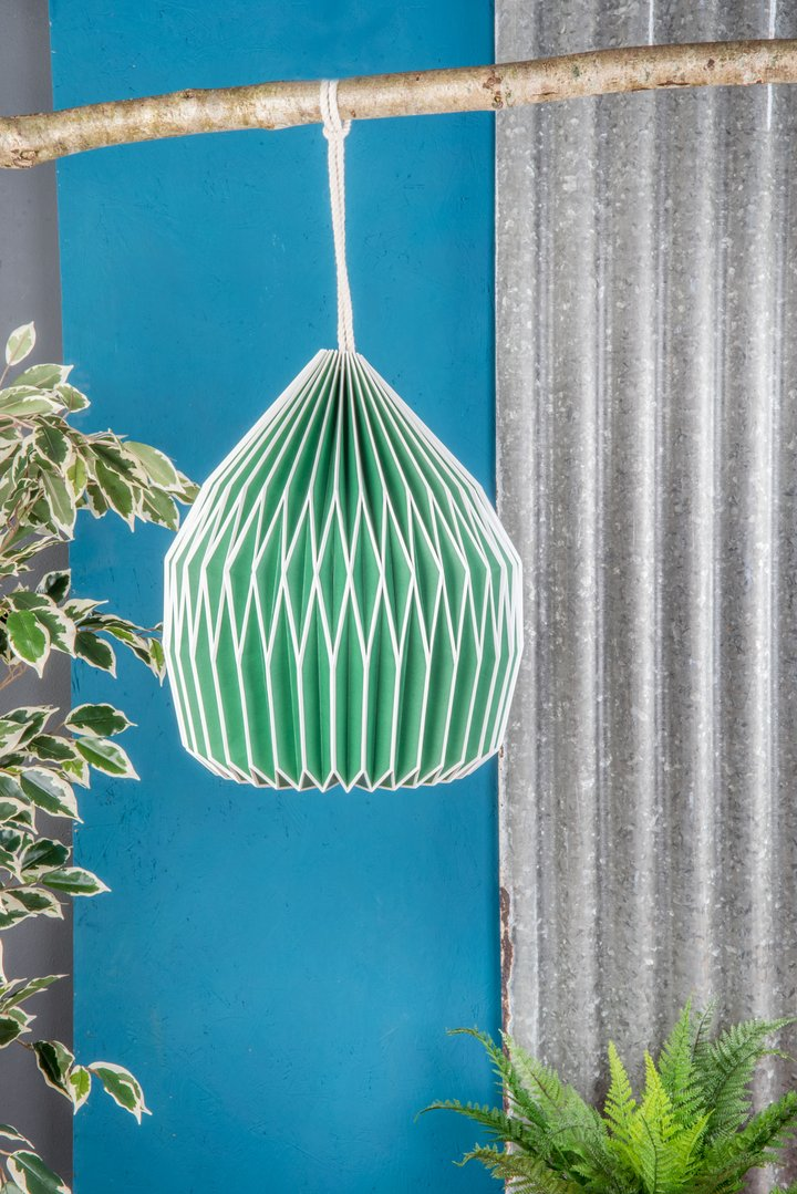 A green pleated paper light shade.  Fairtrade