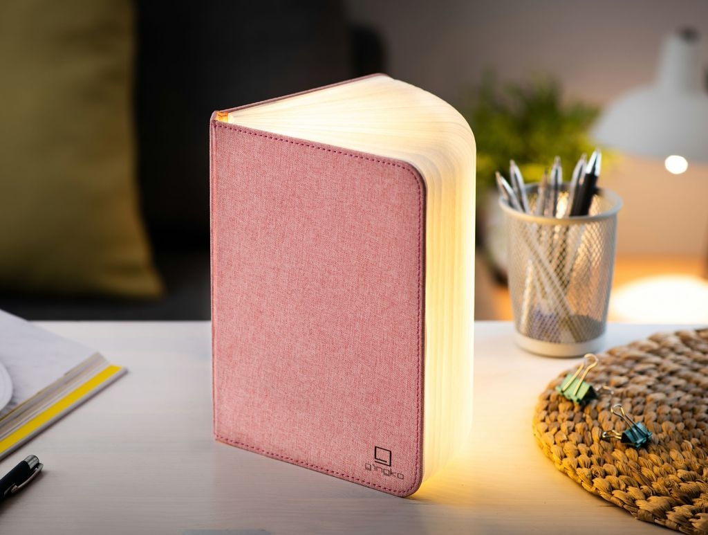 A clever concertina paged light which looks like a book. In linen texture  and blush pink colour. When closed, 9W x 12.2H x 2.5cm