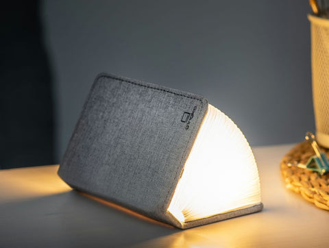 A clever concertina paged light which looks like a book in linen light grey. When closed, 9W x 12.2H x 2.5cm