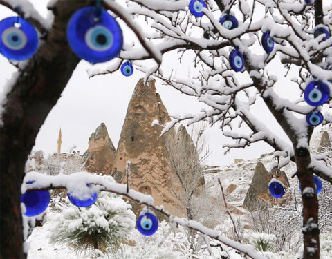 Evil eye discs were hung on a snowy tree amid the famous volcanic rock formations of Cappadocia, a region in Turkey